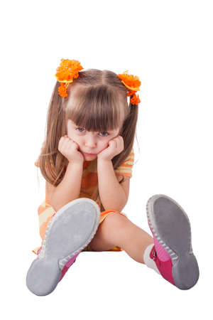 Portrait of unhappy little girl sitting on floor. Isolated on white Imagens