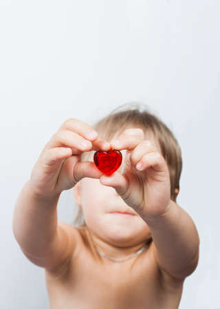 girl looking through red glass heart-shape stone photo