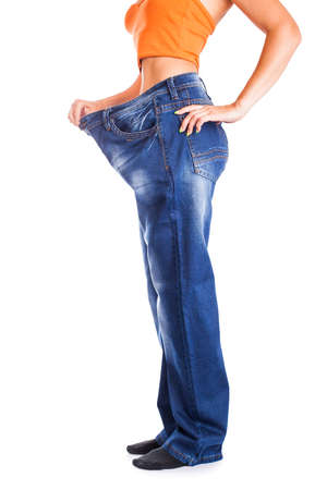 Slim girl in big jeans isolated on white photo