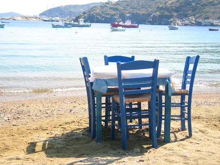 A restaurants table and chairs on the beach, Faros village, Sifnos island, Greece Stock Photo