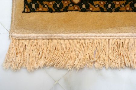 rug weaving: The corner close-up of a floor carpet Stock Photo