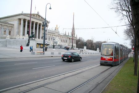 Viennas ring road (with a tram and a car passing by) at the point of the Austrian parliament