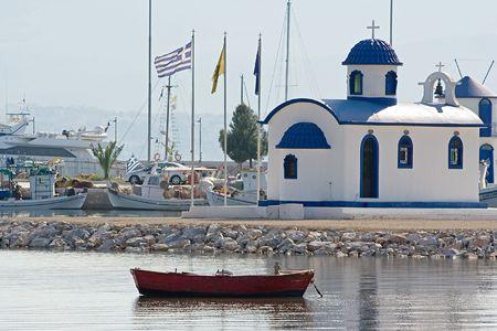 Boat anchored in front of a little church in Nea Artaki, Greece photo