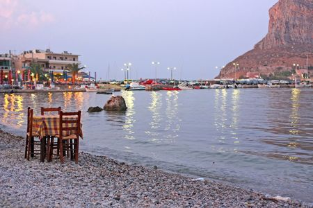 A restaurant table and chairs by the sea of Monemvasia, Greece (focus is on the tablechairs) Stock Photo