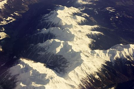 sidelit: A covered with snow range of the Alps seen from an airplane flying above