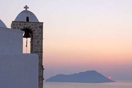 The steeple of a church in the Greek island of Milos during the sunset Stock Photo