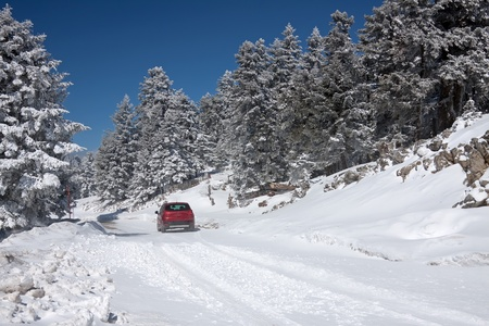 A car in a snow-covered road of mount Parnassos, central Greece