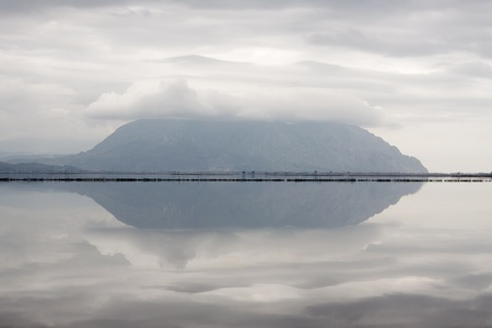 mirroring: The totally calm water of the lagoon of Mesologgi (Greece), mirroring a distant mountain Stock Photo