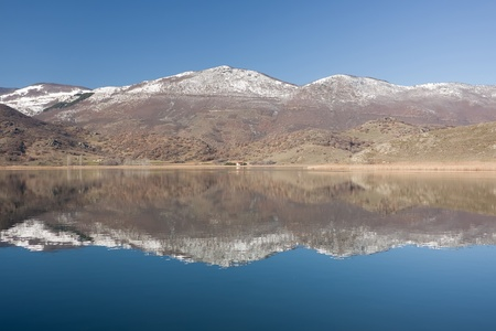 꼭대기가 눈으로 덮인: The calm waters of Zazari lake, northern Greece, with snow-capped mountains in the background