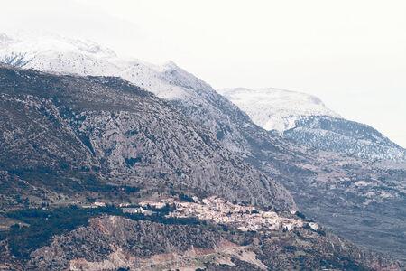 꼭대기가 눈으로 덮인: The village of the ancient site of Delphi below the snow-capped peaks of Mountain Parnassos, Greece
