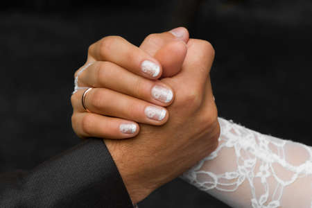 Hands of a groom and a bridegroom close-up. Concept of conflict of opposites photo