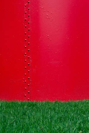 clincher: The background with red metal surface and green grass