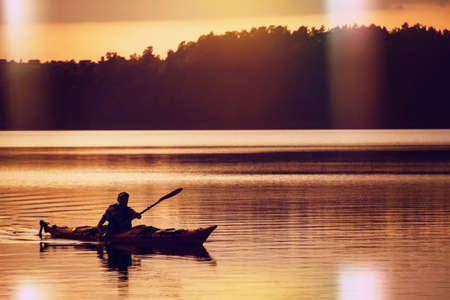 care about the health: The man rowing oars in boat of kayak type on the lake at early evening. Golden sunset.Summer time, active recreation. Healthy lifestyle and care about mental health, resting in  privacy and peace. Stock Photo