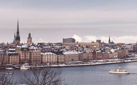 tinted: Vintage tinted snapshoot  Winter view over strait of Stockholm downtown. Boat onth water. Sweden Stock Photo