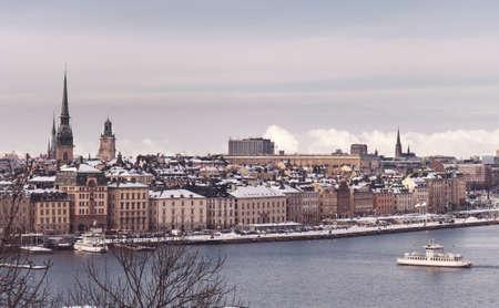 Vintage tinted snapshoot  Winter view over strait of Stockholm downtown. Boat onth water. Sweden Reklamní fotografie - 58869697