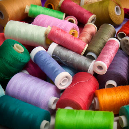 Snapshot of the pile of colorful spools of thread. Sewing conceptual background. 免版税图像