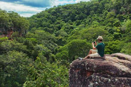 若者観光 sittig 緑 trcal バレーのスマート フォンで山と撮影写真の上部の岩の上。t シャツ、ショート パンツと帽子と 25-30 歳。