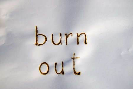 The words burn out have been burnt in white paper