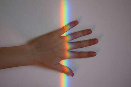 A girl's hand under a rainbow line Stock Photo