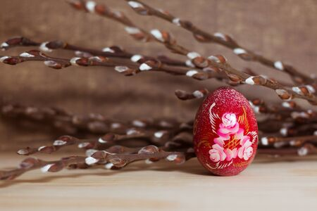 colored Easter red egg with hand-painted willow branches on a woody background.