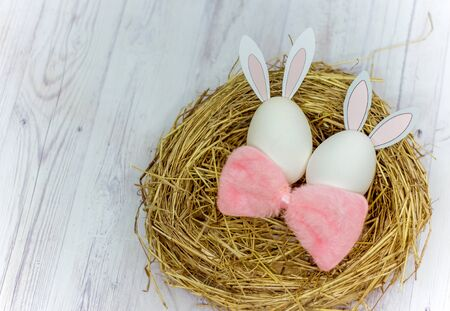 white Easter eggs with rabbit ears in the nest on a wooden table