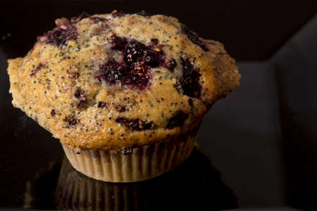 A freshly baked blackberry muffin on a black backgroundFreshly baked blueberry muffins on a black background Stock Photo