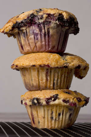A trio of freshly baked blueberry muffins stacked on top of each otherA trio of freshly baked blueberry muffins stacked on top of each other Stock Photo