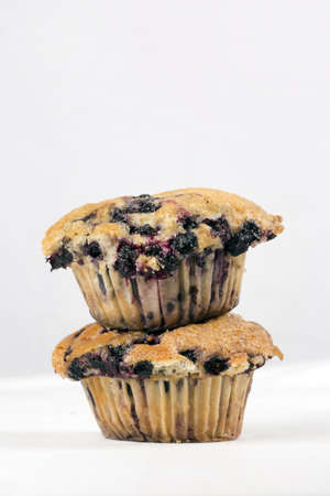A trio of freshly baked blueberry muffins stacked on top of each otherFreshly baked blueberry muffins