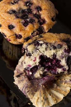 Freshly baked blueberry muffins on a black background