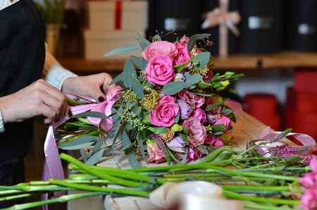 Woman florist tying the ribbon on the bouquet of roses