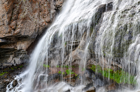 A beautiful mountain landscape. Mountain waterfall Girls braids. Russia.