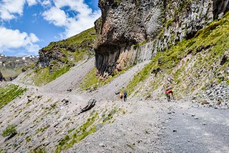 A beautiful mountain landscape. Tourists go along the mountain road. Stock Photo