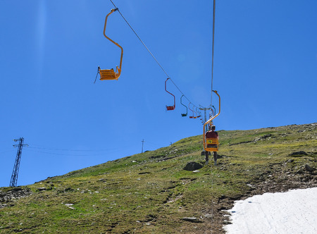A man is riding a chairlift to a mountain
