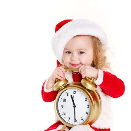 Portrait of little cute girl in santa hat holding big clock on white  photo