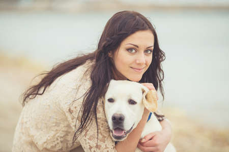 Portrait of beautiful young woman playing with dog on the sea shore photo