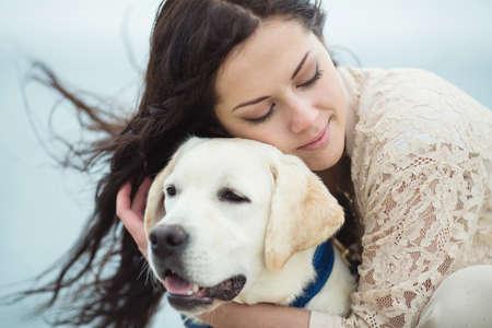 Portret van het mooie jonge vrouw spelen met hond op de overzeese kust Stockfoto