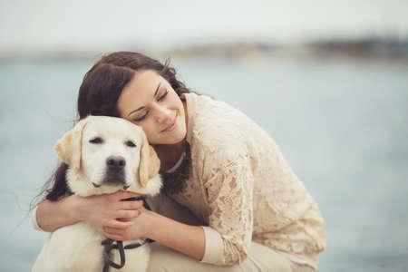 Portrait der schönen jungen Frau, die mit Hund am Ufer des Meeres Lizenzfreie Bilder