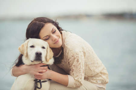 Portrait of beautiful young woman playing with dog on the sea shore
