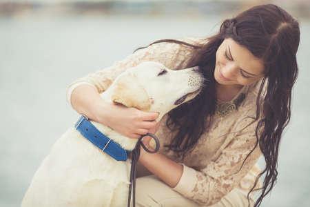 perro labrador: Retrato de la hermosa mujer joven que juega con el perro en la orilla del mar