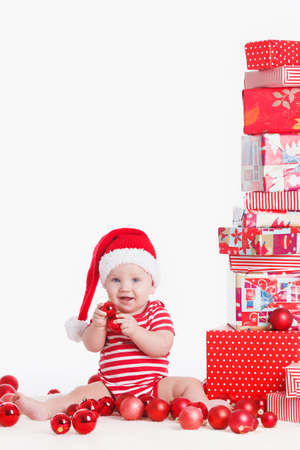 christmas baby: Adorable child is sitting on floor, wearing red Christmas cap, red balls and presents around  isolated on white background