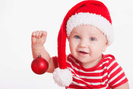 Adorable child is sitting on floor, wearing red Christmas cap, red balls and presents around  isolated on white background photo