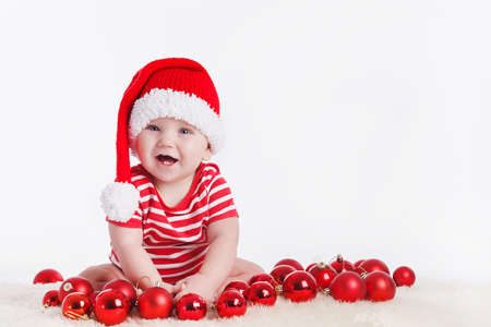 christmas baby: Adorable child is sitting on floor, wearing red Christmas cap, red balls around  isolated on white background Stock Photo