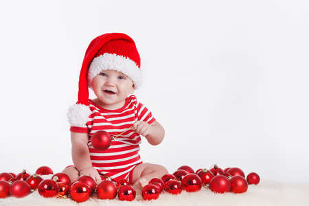 Adorable child is sitting on floor, wearing red Christmas cap, red balls around  isolated on white background photo