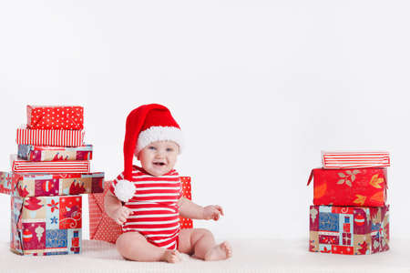 Adorable child is sitting on floor, wearing red Christmas cap, ired balls and presents around  isolated on white background photo