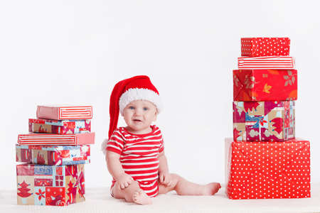 Adorable child is sitting on floor, wearing red Christmas cap, ired balls and presents around  isolated on white background Stock Photo