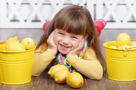 little cute girl with lemons in two yellow buckets photo