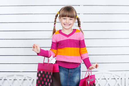 Happy child with shopping bags  She is enjoying the gifts and holidays photo