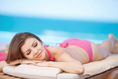 Woman sunbathing in bikini at tropical travel resort  Beautiful young woman lying on sun lounger near pool  photo