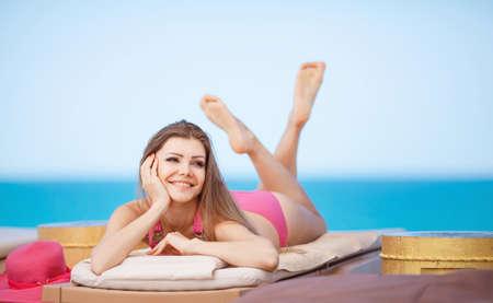 Woman sunbathing in bikini at tropical travel resort  Beautiful young woman lying on sun lounger near pool  photo