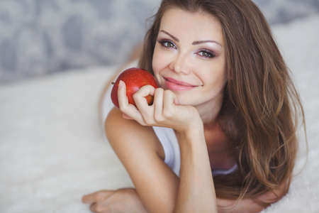 Portrait of lovely young woman holding a fresh ripe apple and smiling photo